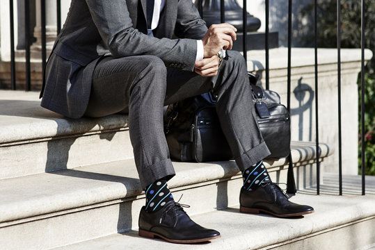 Man in suit sitting on stairs