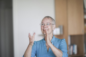 Smiling woman standing in her living room clapping
