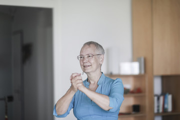 Smiling woman standing in her living room with her hands clasped