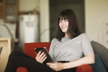 Smiling Woman sitting in an armchair using a digital tablet