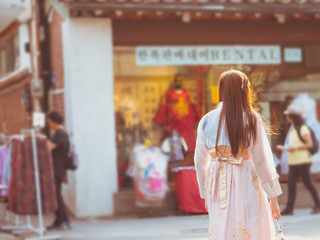travel and tourist asia concept from beautiful woman in korea traditional cloth (hanbok) relax, take picture in vintage town with soft focus dress rental shop background
