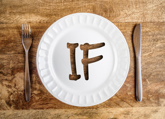 IF letters on white plate with fork and knife on wooden table, top view, intermittent fasting concept