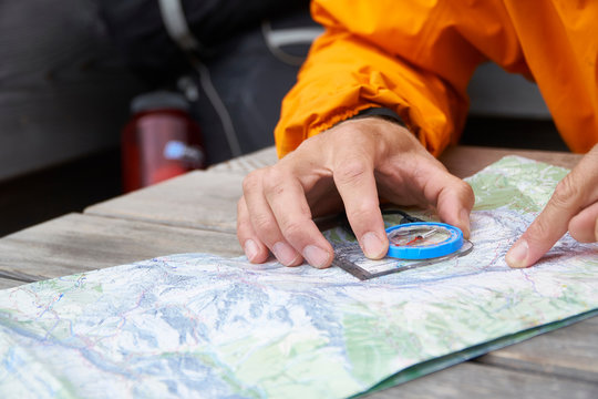 Hiker reading map with compass