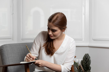 Woman writing on notepad with pencil