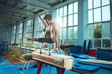 Foto auf Leinwand Gymnastik The sportsman during difficult exercise, sports gymnastics