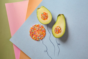 Composition with halves of ripe avocado and sprinkles on color background