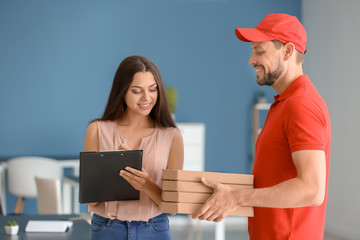 Man delivering pizza to customer indoors