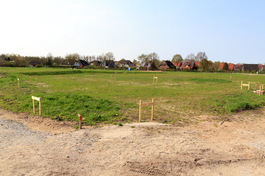 Building lot site with grass after stakeout measurement survey ready for construction, Germany
