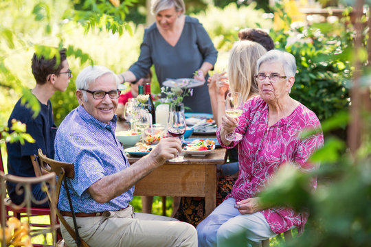 Summertime, cheerful family gathered for picnic in the garden