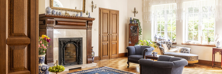 Blue armchairs next to fireplace in elegant living room interior with settee and windows. Real photo