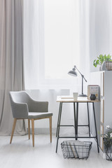Workspace by the window with an industrial lamp on a wooden desk and a stylish armchair in a bright living room interior