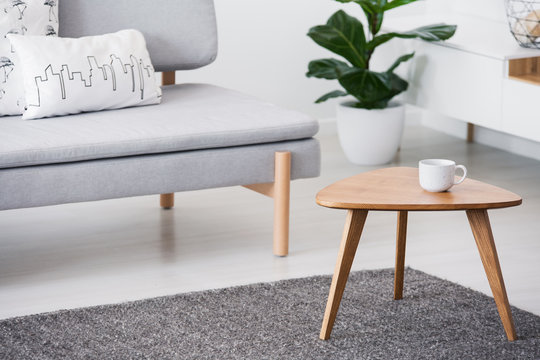 Cup on a wooden coffee table and blurry foreground with graphic pillows on a gray sofa in a white living room interior