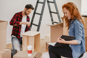 Redhaired woman looking at photobook while furnishing the flat with husband