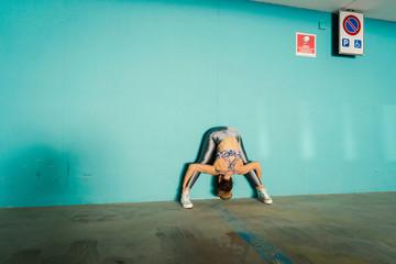 Woman practising yoga in parking lot
