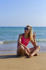 A girl in a swimsuit posing on the beach on a sunny day