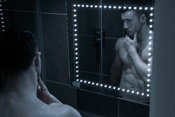 Handsome, sexy, topless, shirtless man stands in front of bathroom mirror imspecting his beard in reflection
