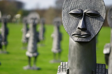 Statue or sculpture of weird faces in a garden, photo taken in Yorkshire Sculpture Park, Wakefield, England, United Kingdom