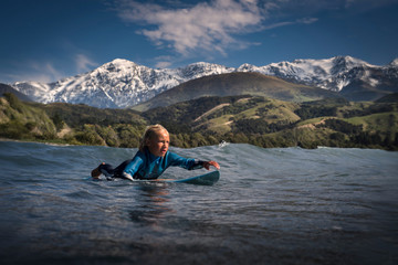 Young boy paddling on surfboard in sea, Kaikoura, Gisborne, New Zealand