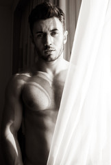 Naked, sexy hunky man with beard and six pack abs stands behind curtains