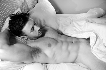 Shirtless sexy hunky man with beard and six pack abs lies naked in bed