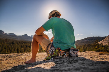 Young male climber sitting on top of rock formation, Tuolumne Meadows, upper part of the Yosemite National Park, California, USA