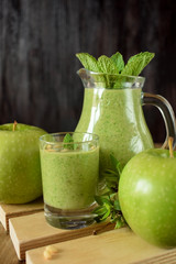 Green smoothie in a glass and in a jug against the wooden background