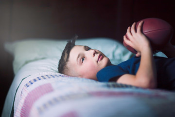 Boy on bed with american football
