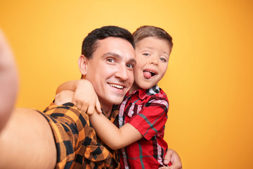 Little boy and his dad taking selfie on color background