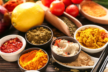 Bowls with different spices on wooden table, closeup