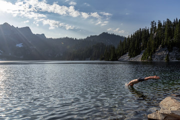 Man diving into pristine alpine lake surrounded by pine forest.