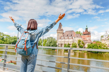 a young happy traveler girl stands on a background of Vajdahunyad castle and lake in Budapest