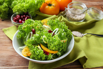 Plate with healthy vegetable salad on wooden table