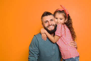 Little girl hugging her father on color background