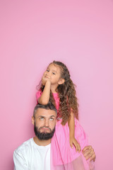 Portrait of father and his little daughter on color background