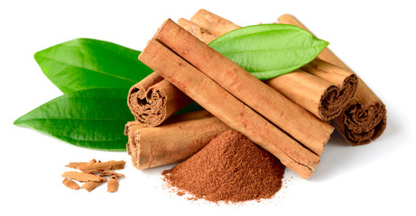 cinnamon powder and sticks with fresh leaves isolated on the white background