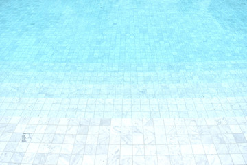 Background of a blue tiled pool with clear cool rippling water