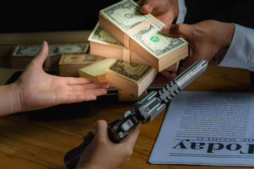 Businessmen pay the dollar To others Because forced and intimidated by guns. with black background to Dark business concept.