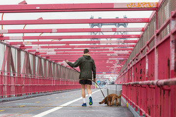 Unrecognizable sporty recreational male jogger with his dog on a leash at Williamsburg bridgein New York CIty, USA.