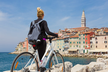 Young active female tourist cycling and enjoiying beautiful view of Rovinj, Istria, Croatia.
