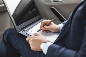 Man in a business suit write on notebook with laptop in the car