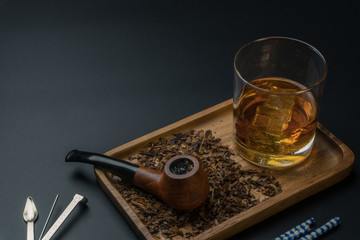 a smoking pipe with tobacco and a glass of whisky in wooden tray, a tamper tool and pipe cleaners on the black table