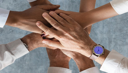 Two men and two women keep their hands on top of each other over a grey background