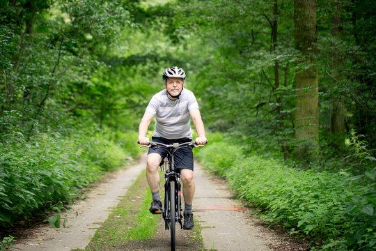 Senior man on a bike during lovely summer time in forest, smiling, enjoying trip