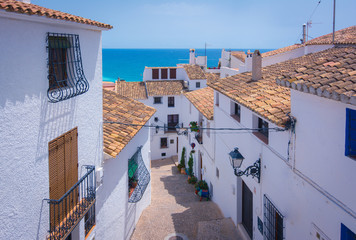 Picturesque narrow street with white houses in village of Altea, Alicante, Spain. Travel and vacation concept. Altea is a mediterranean town in the heart of Costa Blanca