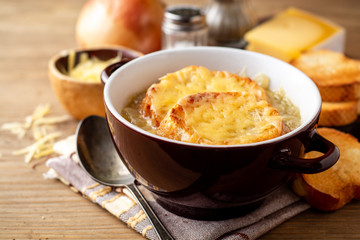 French onion soup with croutons and cheese on rustic wooden table