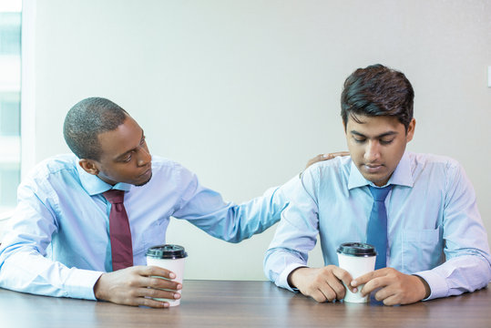 Sad business colleagues discussing bad news during coffee break. Afro American employee expressing support to coworker and patting on his back. Sympathy concept