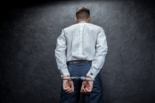 A businessman in handcuffs stands with his back