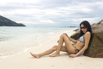 Young slim Asian woman wearing bikini lying on sea rocks, sea and waves as background. Beach and natural in summer.