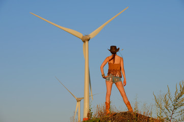 A young woman dressed as a cowgirl takes time out and enjoys the sunset and the new way of getting  alternative energy from power windmills that stand  in front of her in the distance.