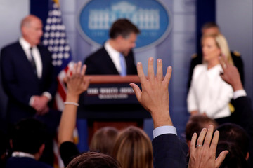 A reporter raises his hand in the White House press briefing room at the White House in Washington